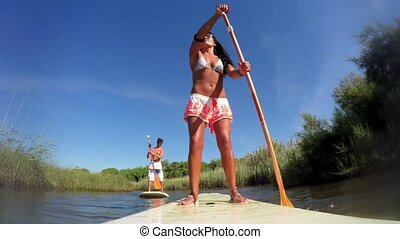 Woman stand up paddleboarding on lake. Young girl doing...