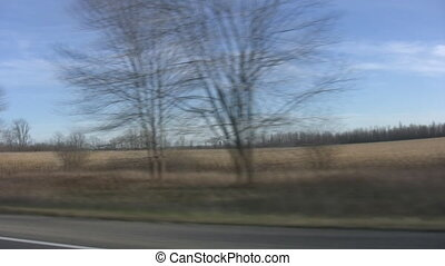 Driving past winter fields.