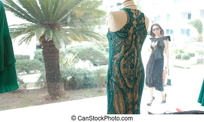 A woman stands in the summer and looks at the dress in the...