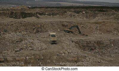 Two trucks and excavator in a quarry - Excavator working in...
