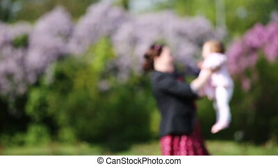 Happy mother and cute baby-girl playing together in a park against beautiful flowers.