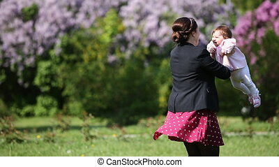 Happy mother and cute baby-girl playing together in a park against flowers.