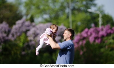 Happy father holding little baby-girl in arms and playing...