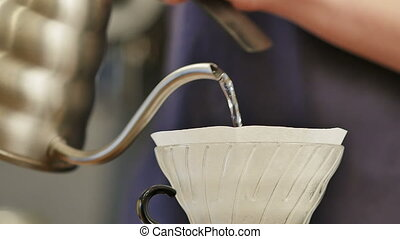 Preparing coffee in a manual filter pouring boiling water...