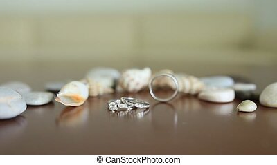 Wedding rings on the table with seashells. Maritime...
