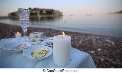 Dinner by the candlelight on the beach. A table for a...