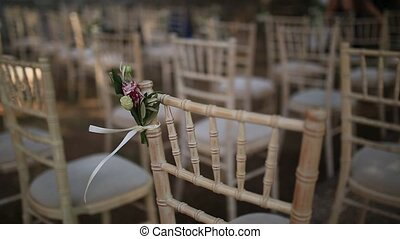Chairs at a wedding ceremony. Decorated with flower...