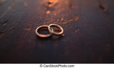 Wedding rings on dark wooden texture at sunset. Wedding...