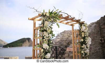 Wooden arch for the wedding ceremony at sunset. On the shore...