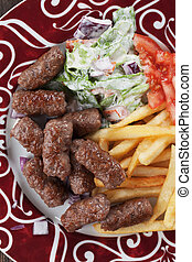 Cevapcici, bosnian minced meat kebab with french fries and...