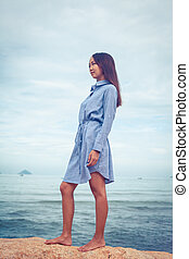 A portrait of beautiful asian woman in dress stand on a stone by the sea