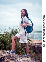 Asian woman with backpack in white dress climbing on mountain near the sea