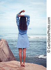 Asian woman in dress back stand and rise hands on a stone by the sea