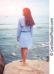 A sunny portrait of asian woman in dress back stand on a stone by the sea