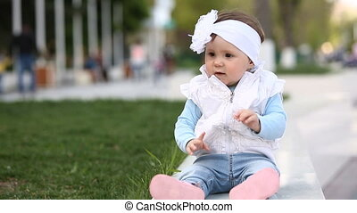 Cute baby-girl sitting in the green grass in the city park...