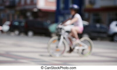 Happy little girl riding a bicycle in the city park at...