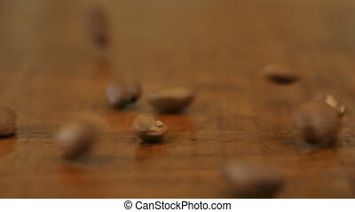 Coffee beans on wooden table. Close up. Slow motion....