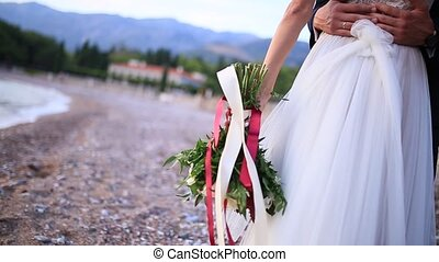 Wedding bouquet in hands of the bride on the beach Milocer Park