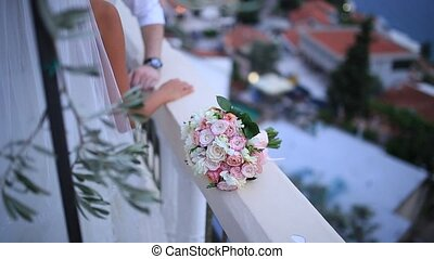 Wedding bouquet of pink roses on a stone fence with columns fenc