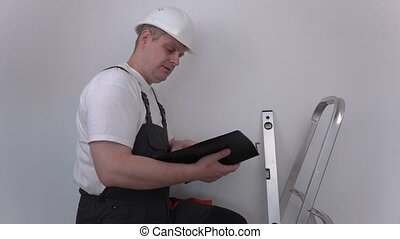Builder reading and show thumb up near stairs