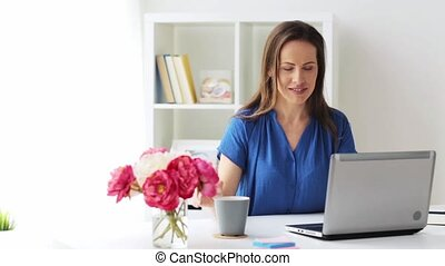 woman with laptop and coffee at home or office - business,...