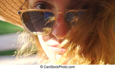 Cutie young girl in sunglasses posing and looking at the...