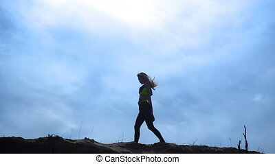 Silhouette sport girl walks on top of a hill outdoors