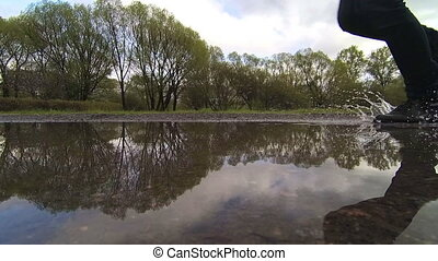 man runs through puddles in the park. Feet closeup. slow motion