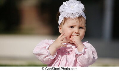 Close-up of the cute little baby-girl eating bake in the...