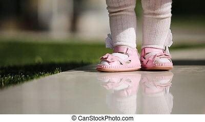 Close-up of the beautiful baby-girl standing in the park at...