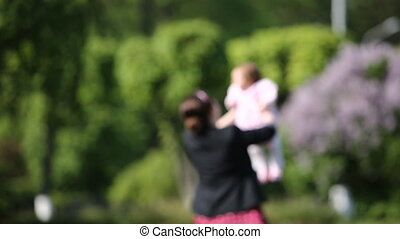 Happy mother and cute baby-girl in the park at sunlight day,...