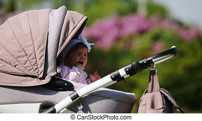 Crying baby-girl sitting in the baby carriage in the park at...