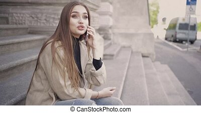 Cheerful girl talking phone outside - Young stylish woman...