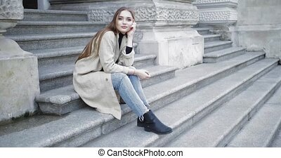 Female posing on stairs - Young stylish female wearing jeans...