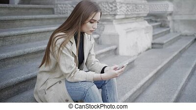 Woman using smartphone while sitting on stairs - Side view...