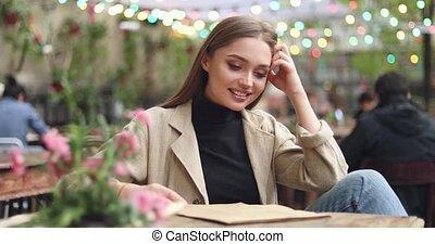 Smiling girl investigating menu - Young beautiful girl...