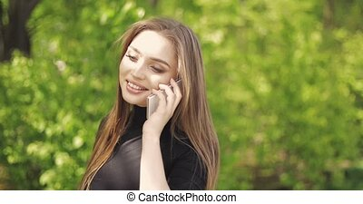 Female talking phone outside - Young stylish woman with long...