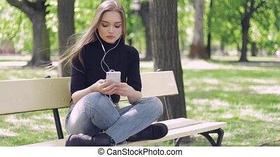 Woman on bench listening to music - Young casual female...