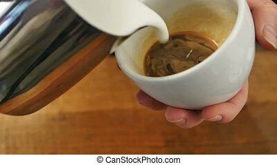 Pouring stream milk into a cup of espresso. Close up. Slow...
