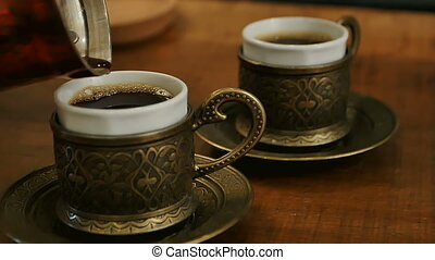 Two cups of black coffee being poured from a turk. Close up....