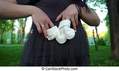 Young happy pregnant woman playing with baby booties on her pregnant belly