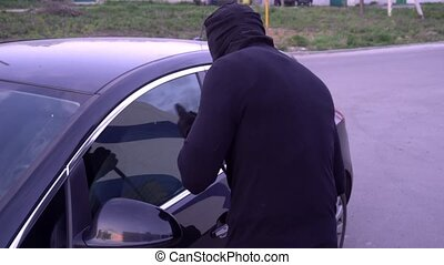 Robber with a crowbar near the car door.