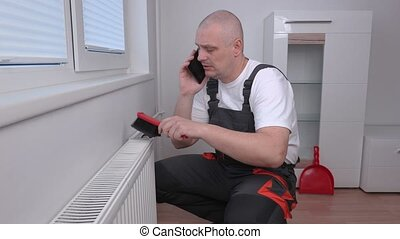 Plumber cleaning radiator and talking on phone