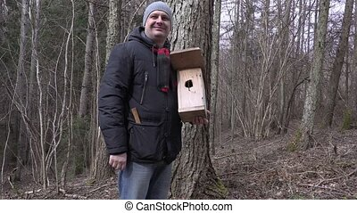 Happy man with birdhouse show thumb up