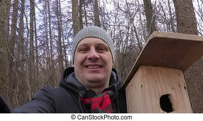 Man with birdhouse try to take selfie