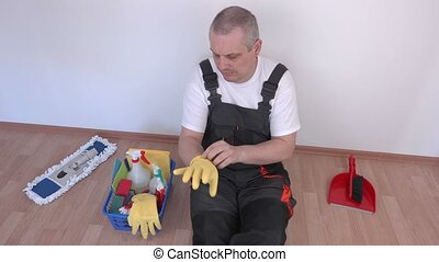 Cleaner sitting on floor and donning rubber gloves
