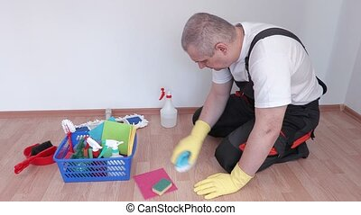 Worker with brush cleaning laminate