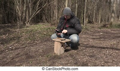 Man using tablet PC near birdhouse