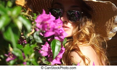 blonde girl in sunglasses and straw hat posing on camera -...
