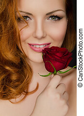 Young woman with red hair holds rose in her hands